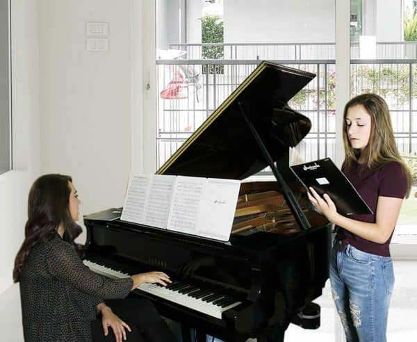 two ladies using sheetminder, singing and playing piano